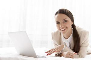 Retrato de feliz empresaria usando laptop en la habitación del hotel foto