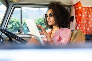 Pretty hipster looking at map in camper van photo
