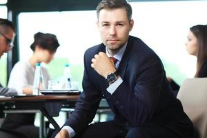 Businessman with colleagues in the background photo