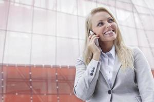 Happy young businesswoman using cell phone against office building photo