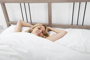 Retrato de joven mujer acostada en la cama