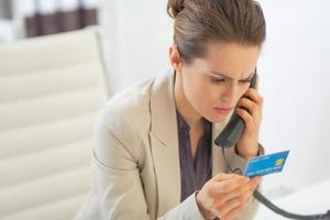 business woman with credit card talking phone in office