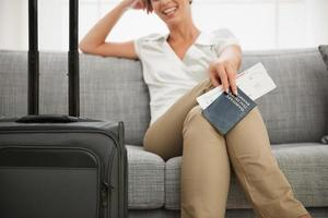 Closeup on passport and ticket in hand of smiling woman