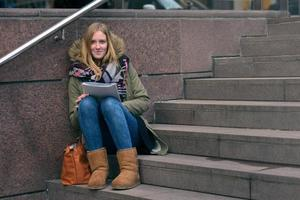 Young woman sitting reading on urban steps