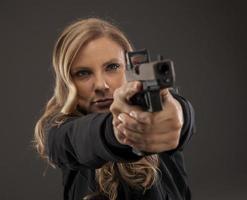centrarse en mujer tirador apuntando arma. foto