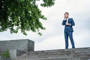 Success ahead. Young man sitting on the stairs businessman drink