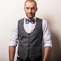 elegante joven guapo en chaleco gris y corbata de moño.