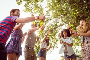 Happy hipsters spraying beer bottles photo