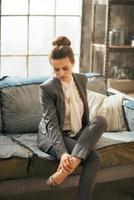 Mujer de negocios pensativa en loft apartamento revisando piernas cansadas