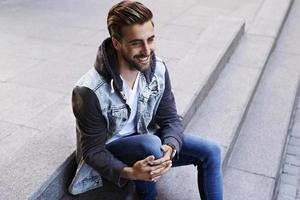 Happy young man on step photo