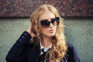 moda joven mujer rubia en gafas de sol en la pared
