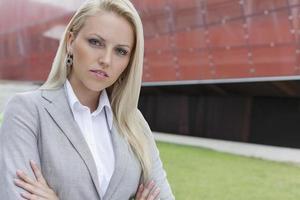 Close-up portrait of confident businesswoman against office building photo