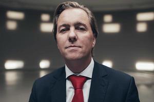 Arrogant entrepreneur wearing suit with red tie in empty room.