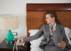 Mujer de negocios contestando llamadas telefónicas en la cama en la habitación del hotel foto