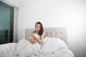 Sad young woman sitting on bed photo