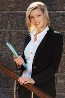 Young businesswoman with a folder against office building