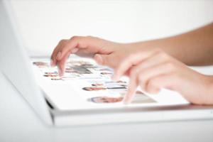 Cerca de manos eligiendo imágenes en una computadora portátil futurista foto