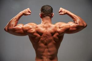 Male bodybuilder flexing his biceps, back view