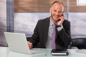 Happy businessman conducting business on his mobile phone