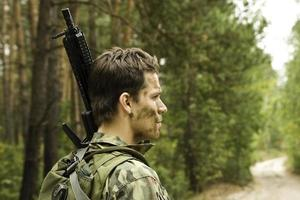 Airsoft player, man in camouflage with gun photo