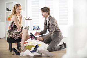 Cliente femenino tratando de zapatos con un vendedor foto