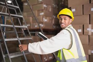 Worker with diary in warehouse