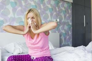 mujer joven que sopla su nariz en papel de seda