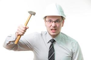 Hombre de negocios enojado en casco blanco con martillo en mano foto