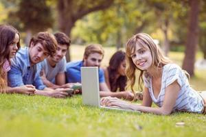 bonita rubia usando laptop en el parque foto