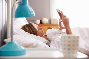 Woman In Bed Looking At Digital Tablet