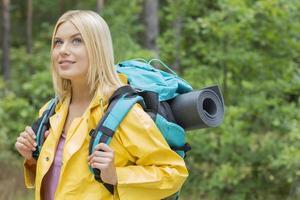 Sonriente mujer mochilero en gabardina mirando a otro lado en el bosque