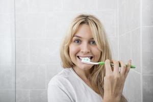 mujer joven cepillarse los dientes en el baño foto