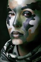 woman with military style clothing and face paint make-up photo