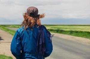 mujer joven de pie junto a la carretera en el país foto