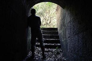 Man stands in dark stone tunnel with glowing end