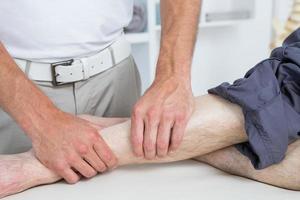 fisioterapeuta fazendo massagem nas pernas para seu paciente