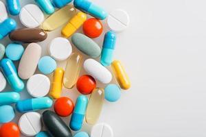 composição com pílulas coloridas e fundo cinza claro.