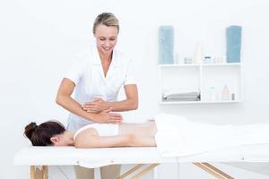 Physiotherapist doing back massage photo