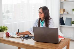 Portrait of physician doctor working in medical office workplace writing