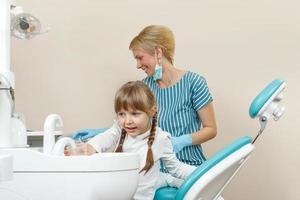 Niña feliz en el dentista. foto