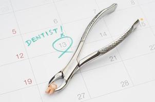 nota de cita con el dentista en el calendario, extracción del diente foto