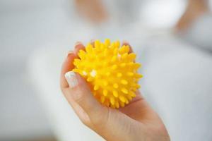 Cerca de mano femenina sosteniendo bola de masaje amarillo foto