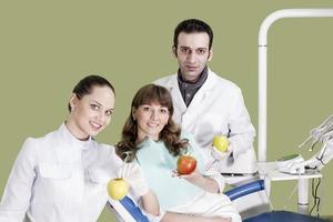 Assistant dentist and the patient hold in hand by apple