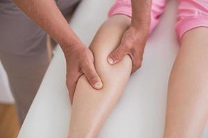 Physiotherapist doing calf massage photo