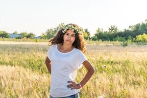 Teen girl with a wreath of daisies in  field