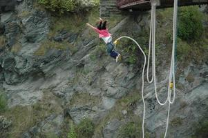 A woman bungee jumping off of a bridge