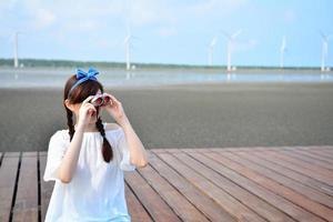 Teenage girl lifted up binoculars