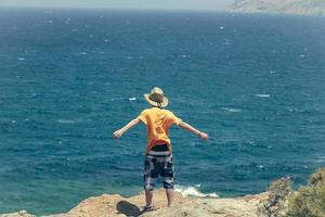 teenager standing on a cliff photo