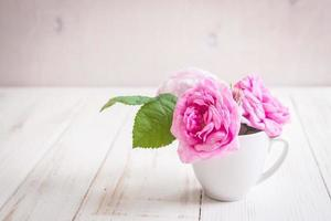 Pink tea roses on a white wooden background photo