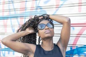 retrato urbano da linda mulher africana com óculos de sol, penteado.